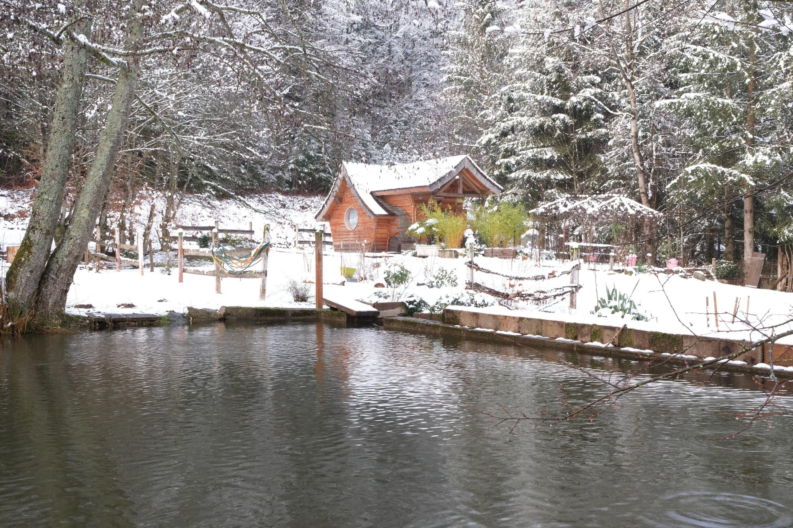 Etang et chalet sous la neige